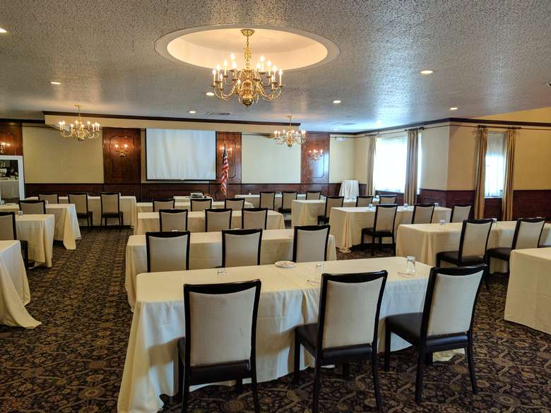 large meeting room set up with tables of three for a conference