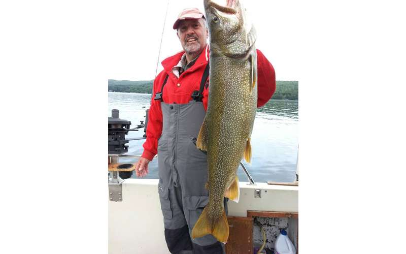 A man in a boat holding a huge lake trout