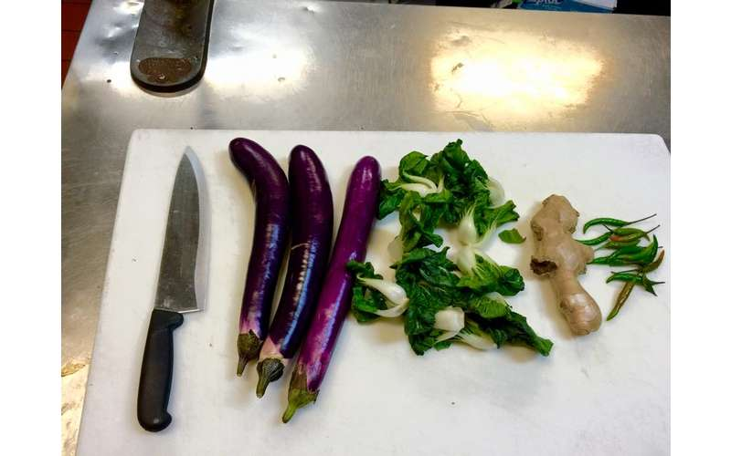 fingerling eggplant and bok choy on a cutting board