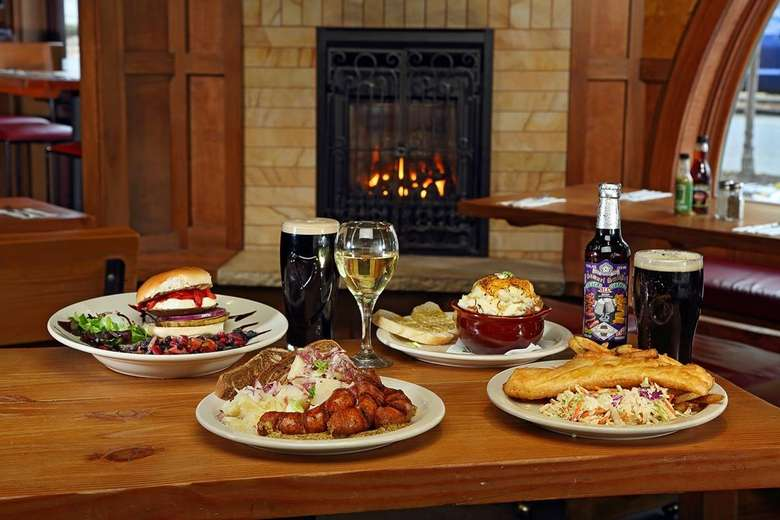 plates of food and drinks on a wooden table in a restaurant, a fireplace in the background