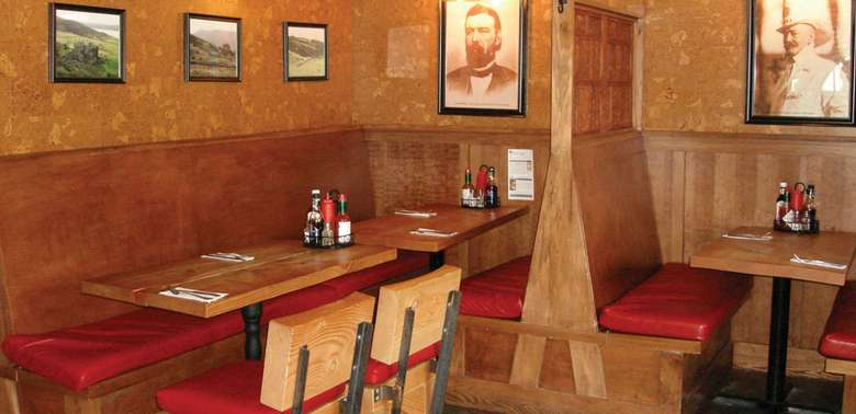 wooden booths with red cushions in a restaurant, photos are on the wall