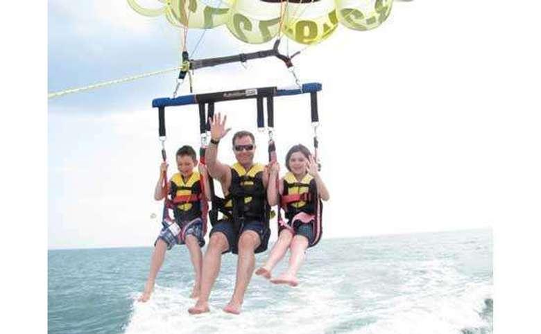 three people parasailing