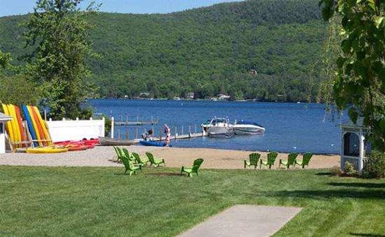 view of boats, dock, chairs, kayaks, lake