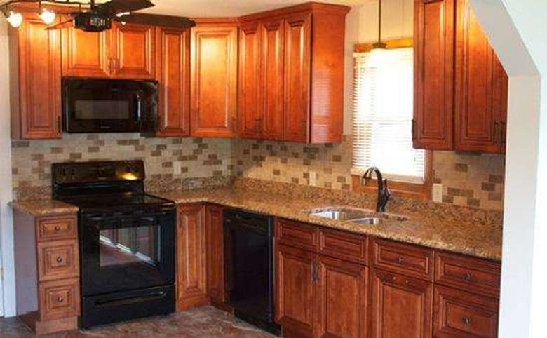 a kitchen with sink, window, cabinets, stove, microwave