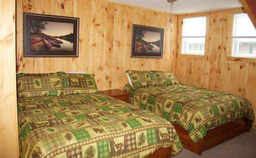 another view of two beds with brown and green Adirondack-style bedspreads
