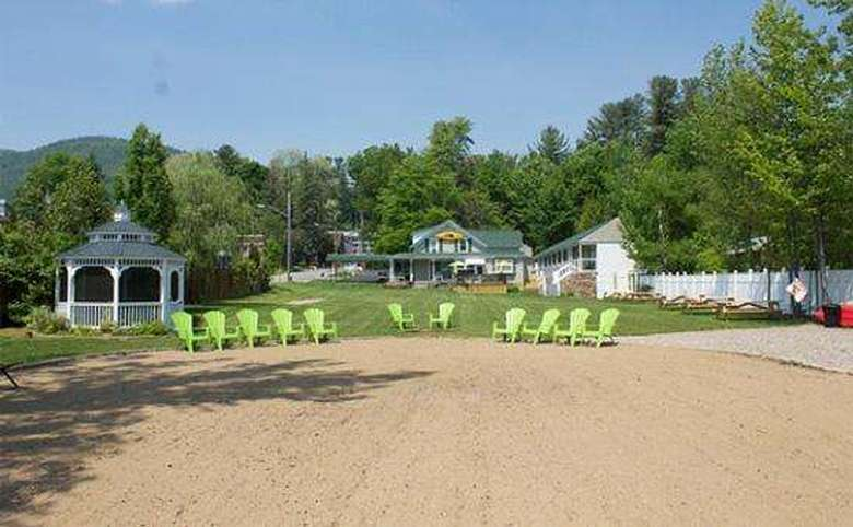 green chairs outside, gazebo on the left, building in the back