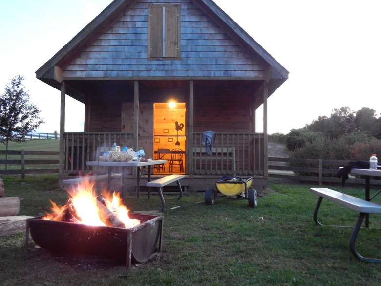 a cabin with a fire pit and tables outside
