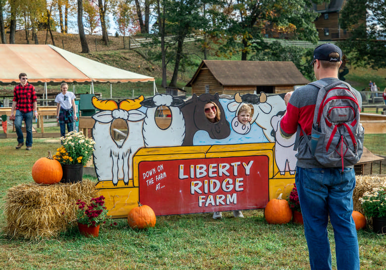 man taking photo of people with heads in cut out image of farm animals