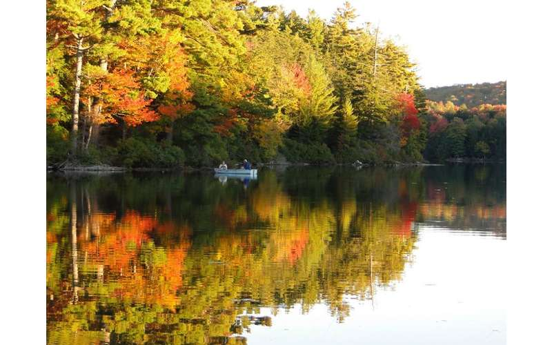two people out on a boat with fall foliage in the background
