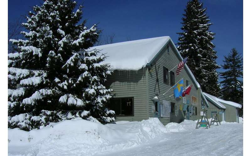 a two-story building surrounded by trees and snow on the ground