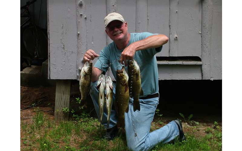 man holding up smallmouth bass
