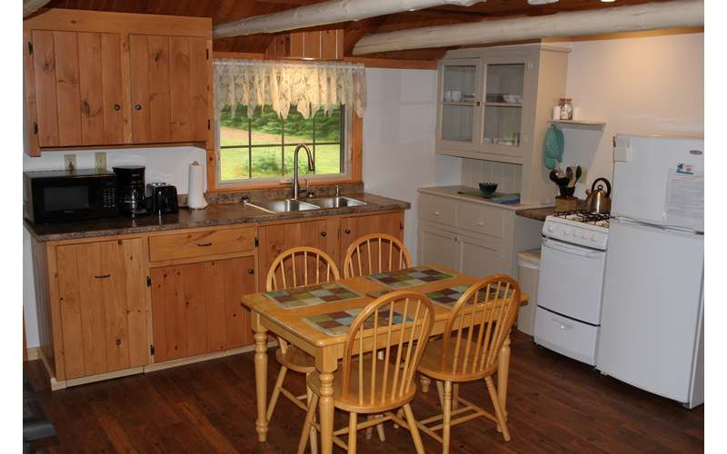 a fully equipped kitchen with a small, four-seat dining table