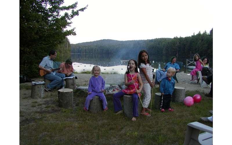 people near a lakeside campfire