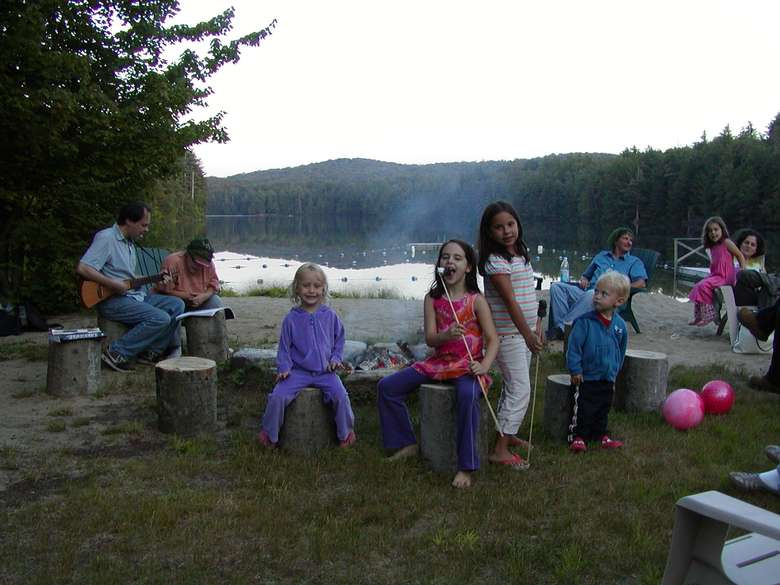 people near a lakeside campfire