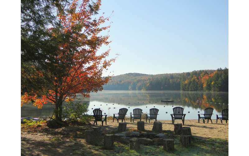 fall lake view with chairs by the shoreline