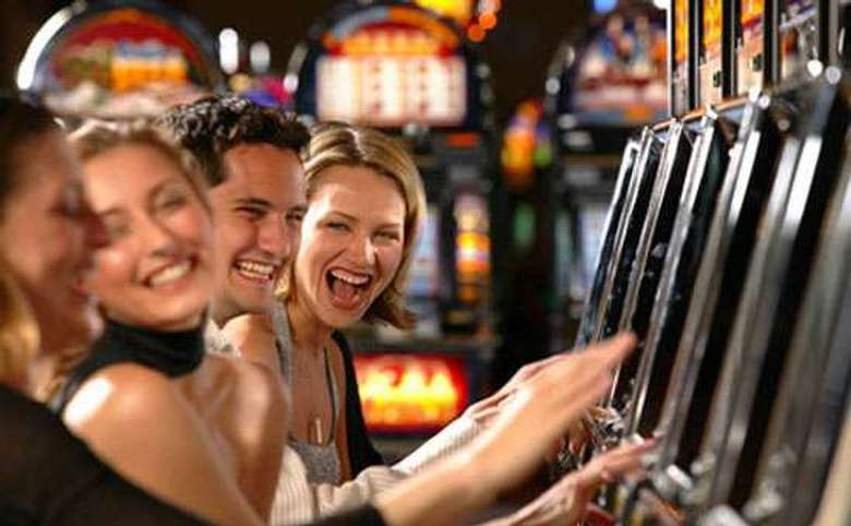 four smiling people using slot machines in a casino
