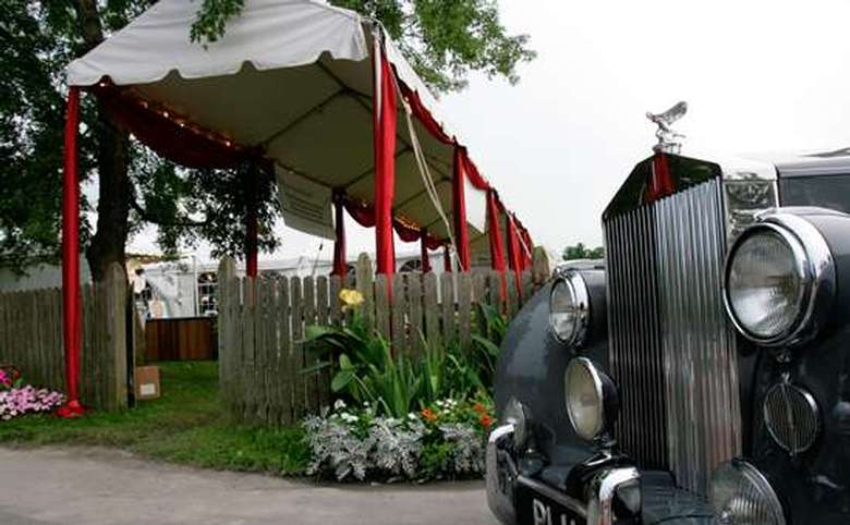 antique car pulled up in front of a white awning with red posts