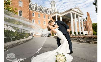 newly married couple kissing in front of Otesaga New York building