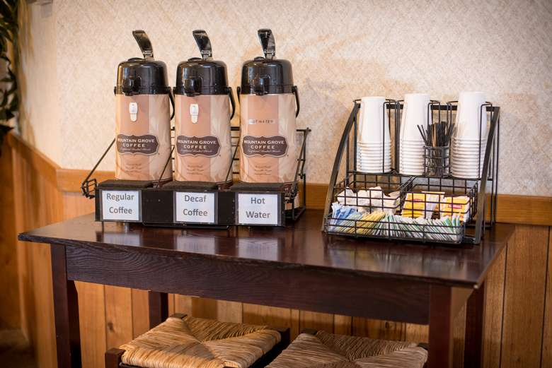 coffee station with three coffee dispensers and stacks of cups