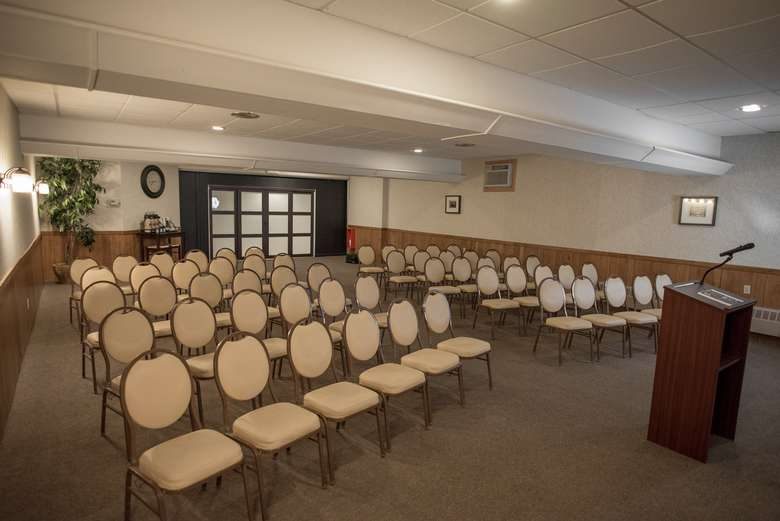 rows of chairs and a podium set up for a presentation