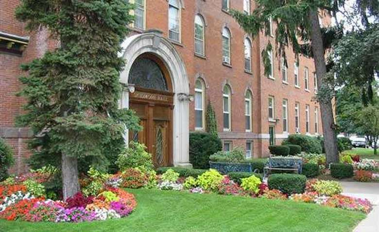 exterior of a large brick apartment building with lots of colorful flowers
