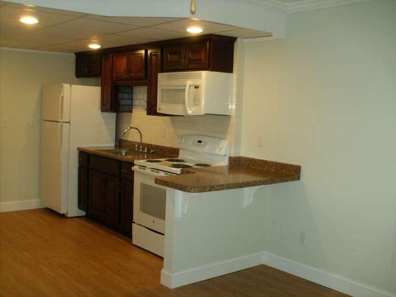 kitchen with white appliances, dark cabinets, and a subway tile backsplash