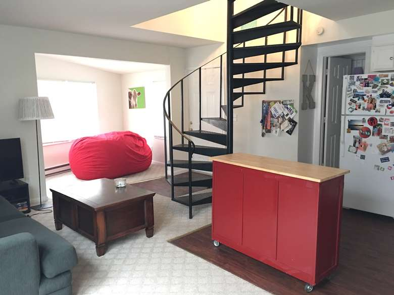 black spiral staircase in the middle of a room with a sitting area, a large red beanbag, and a red moveable countertop