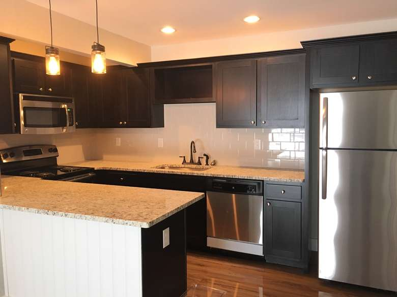 modern kitchen with stainless steel appliances, dark cabinets, and stone countertops