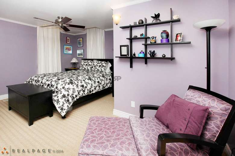 purple bedroom with a black and white bedspread and a pink or purple chair and ottoman