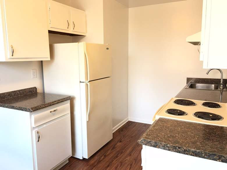 small apartment kitchen with white cabinets, walls, and appliances