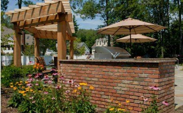 brick wall with a grill built into it, plus a pergola and two umbrellas