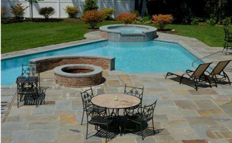 a pool area with a hot tub, fire pit, lounge chairs, and a table