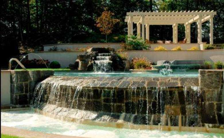 water flowing out of a large pool that also has a waterfall and a pergola in the background