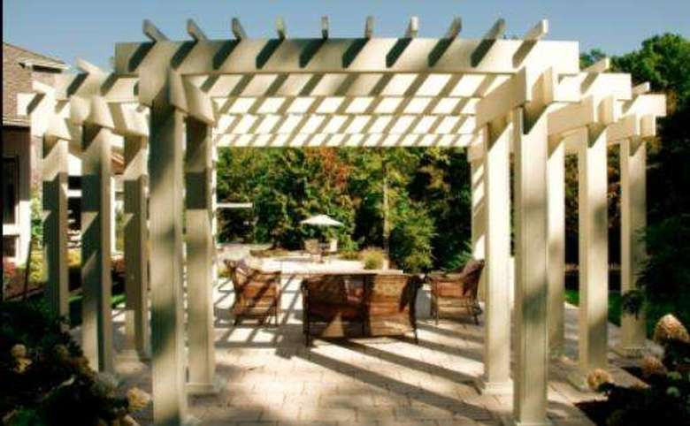 large pergola with a couch and two chairs under it