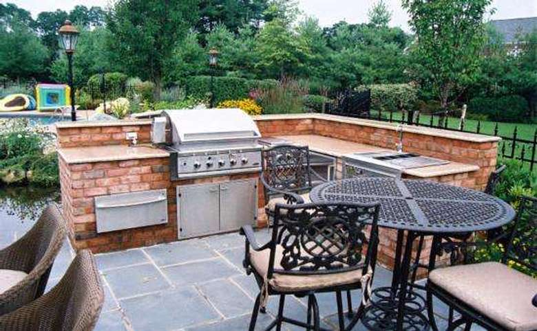outdoor grill station and sink built into a brick wall with a seating area nearby