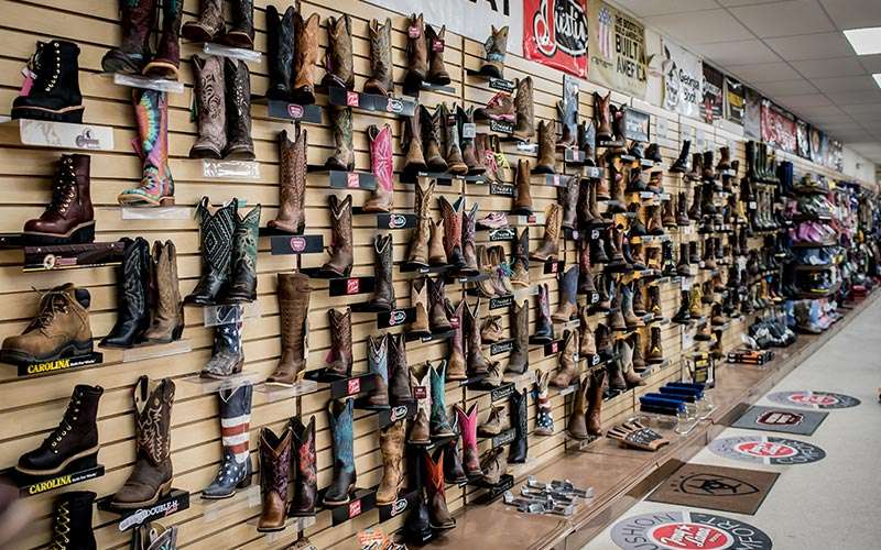 a large display of boots on a store wall