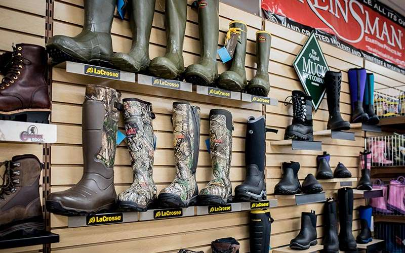 a few rows of boots on a store wall