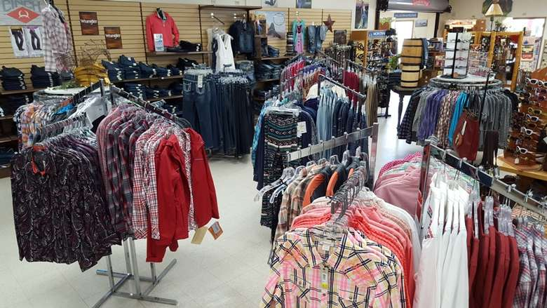 large room with racks of clothing and shirts