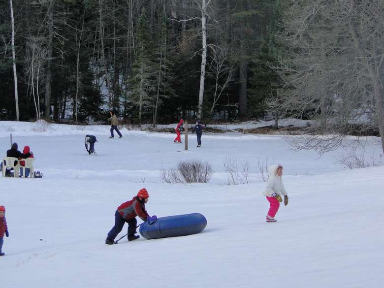 a kid pushing a snow tube, other kids are around