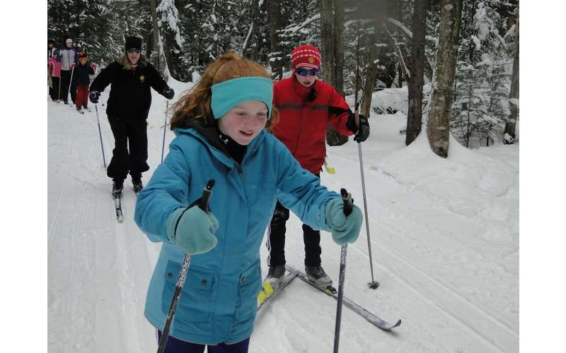 three people cross-country skiing with a young girl dressed in blue in the lead