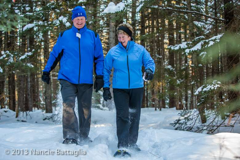 two slightly elderly people cross-country snowshoeing and smiling