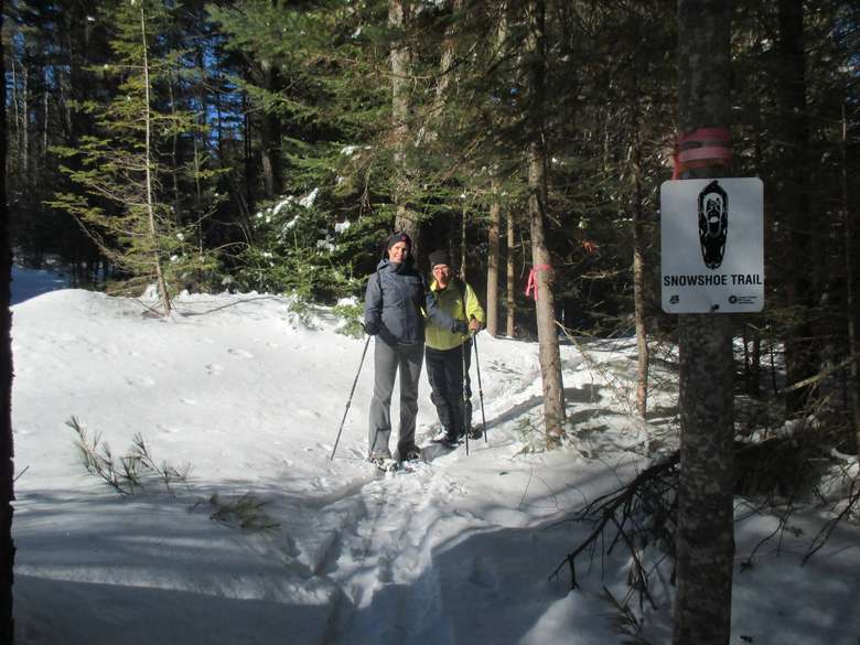 a couple standing by a snowshoeing trail sign