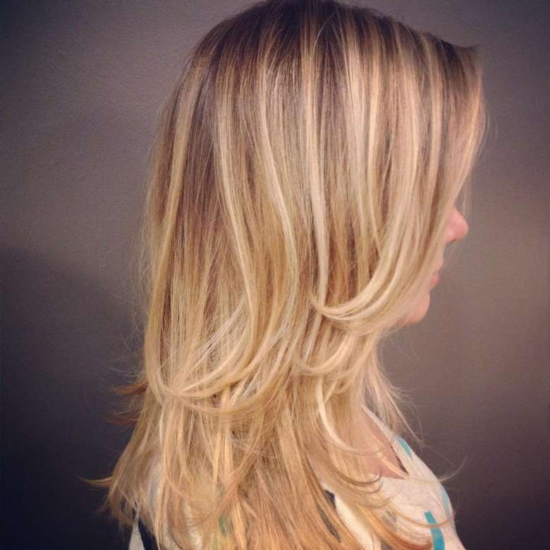 side view of woman's long layered hair with blond balayage hair color