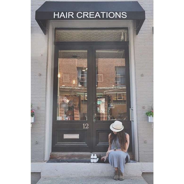 door into the salon with hair creations signage above and young woman sitting on steps