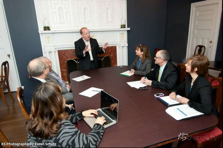 businessman leading a meeting at a conference table
