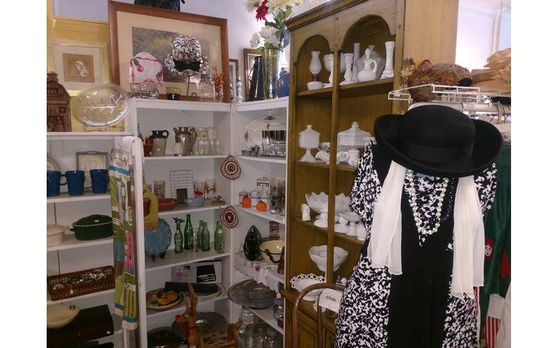 some vintage clothing on display and antique glassware on shelves