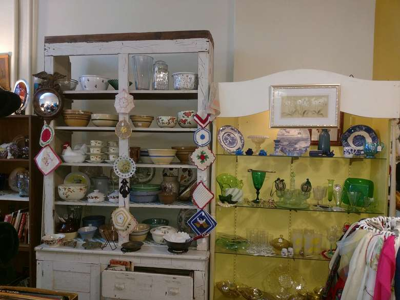 plates, glassware, and other antiques on display inside a store
