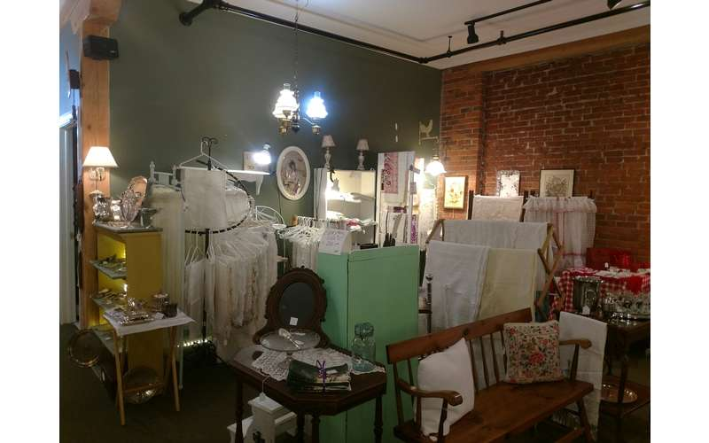 linens, a bench, lamps, and other items on display
