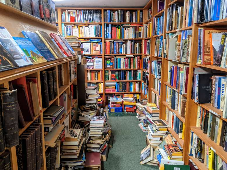 books on shelves and on the floor