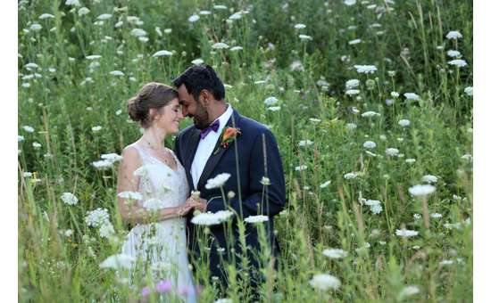 bride and groom in a grassy field